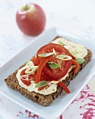 Wholegrain bread topped with hummus (chick-pea spread) & tomatoes