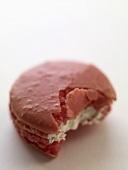 Pink macaron (small French cake), partly eaten