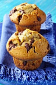 Two chocolate muffins on blue napkin
