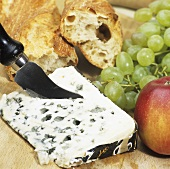 A piece of Roquefort with fruit and baguette