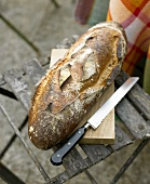 Bread and bread knife on a garden chair