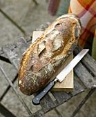 Brot mit Brotmesser auf einem Gartenstuhl