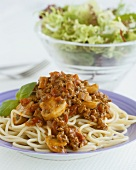 Spaghetti bolognese with mushrooms, salad behind