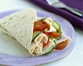Wraps filled with slices of turkey breast, tomato & cucumber