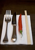 Knife, fork, chilli and chopsticks on napkin