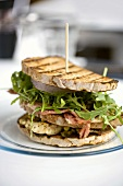 American club sandwich with chicken, bacon and rocket