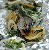 Trout with lime slices and dill in aluminium foil
