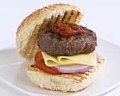Grilled beefburger with cheese and tomato relish in a bun