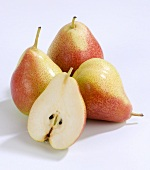 Half a pear in front of whole pears (variety: Blush)
