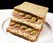 Double-decker corned beef, sauerkraut and gherkin sandwich