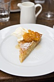 A piece of almond tart with apricots and cream