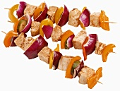 Three grilled chicken and vegetable kebabs