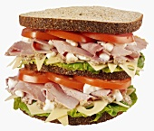 Double-decker ham, cheese, lettuce and tomato sandwich
