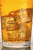 A glass of cider with ice cubes (close-up)