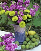Greengages and jug of green chrysanthemums and stocks