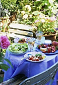 White wine, salad etc. on laid table out of doors