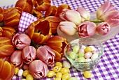 Tulpen und bunte Zuckereier auf karierter Tischdecke