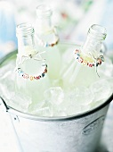 Three bottles of lemonade in an ice bucket