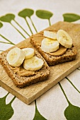 Two slices of rye bread topped with peanut butter & bananas