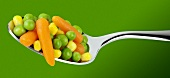 Peas, sweetcorn kernels and carrots on a spoon