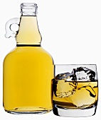 Whisky in bottle and in glass with ice cubes