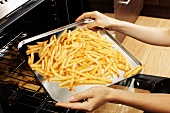Putting a tray of chips into the oven