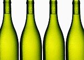 White wine in four green bottles