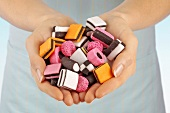 Hands holding coloured liquorice sweets