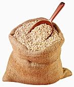 Pearl barley in jute sack with scoop