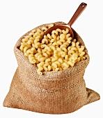 Pasta spirals in jute sack with scoop