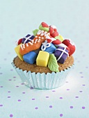 Cupcake decorated with coloured marzipan gifts for Christmas