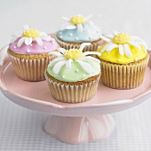 Four cupcakes with daisy decorations on a pedestal stand