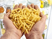 Two hands holding spiral pasta