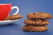 Drei aufgetürmte Chocolate Chip Cookies mit einer Tasse