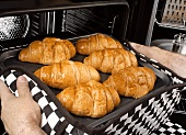 Man taking a tray of baked croissants out of the oven