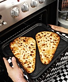 Man taking naan bread out of the oven
