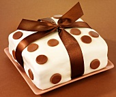 Cake covered in fondant icing, with spots and bow