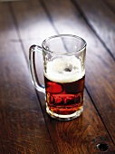 Half-full glass of beer on wooden background