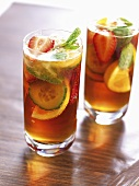 Two glasses of Pimm's cocktail with orange and mint