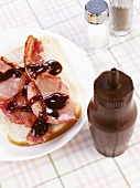 Fried rashers of bacon on white bread with brown sauce