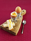 Boiled eggs in eggcups with bread soldiers on wooden board