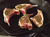 Four raw, marinated lamb chops in a grill pan