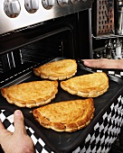 Man taking Cornish pasties out of the oven