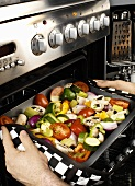 Man putting mixed vegetables into the oven