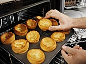 Man taking baked Yorkshire puddings out of the oven