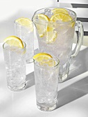 Water in glasses and jug, with ice cubes and lemon slices