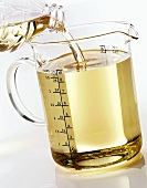 Pouring corn oil into a measuring jug