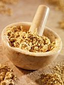 Crushed fenugreek in and beside a mortar