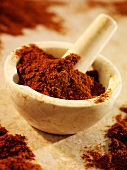 Ground paprika in and beside a mortar