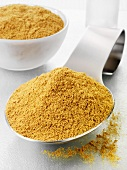 Ground cumin on a spoon and in a glass bowl
